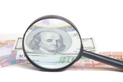 Banknotes of different countries under a magnifying glass isolat Stock Image