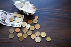 Banknotes, dollars, and coins of different countries on the background of a wooden table. Next to the glass jar with the royalty free stock image