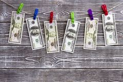 Banknotes of dollars hanging on a rope on clothespins. On a wooden background Royalty Free Stock Photography