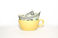 Banknotes dollars in yellow cup on a white background Stock Photography
