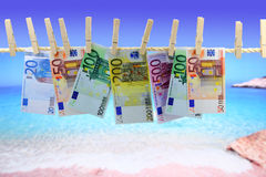 Banknotes in front of the beach. Banknotes hanging on clothesline in front of the beach Royalty Free Stock Photos