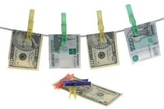Banknotes are hooked clothespins on a rope. On a white background Royalty Free Stock Image