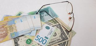 Hryvnia dynars and dollars near eyeglasses on white table royalty free stock photography