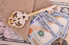 Banknotes hundred dollars, burlap and key. Stock Photos