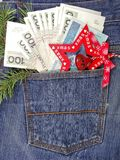 Banknotes in jeans pocket on Christmas gifts - Christmas shopping Stock Images