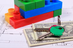 Banknotes, keys and building blocks on drawing of house Stock Photo