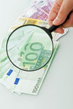 Banknotes and magnifying glass Stock Photos