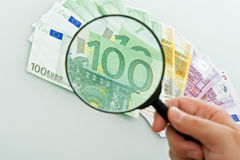 Banknotes and magnifying glass Stock Photography