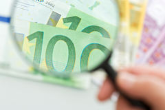 Banknotes and magnifying glass Royalty Free Stock Photography