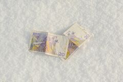 Banknotes of the old swedish krones in snow Royalty Free Stock Photos