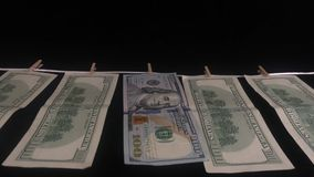 One hundred dollars banknotes weigh on a rope in a row with clothespins. Banknotes of one hundred dollars hang on a rope with clothespins. The concept of dirty stock video