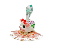 Banknotes and piggy bank. Piggy bank and currency notes in isolation on a white background closeup Royalty Free Stock Image