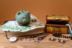 Banknotes, piggy banks and jewelry in a box Royalty Free Stock Photos