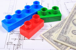 Banknotes and plastic building blocks on drawing of house Stock Image