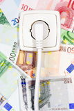 Banknotes and Power socket. Plugged power cable isolated on a money background Stock Photography