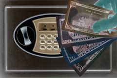 Banknotes of US dollars in a male hand against the background of a safe cell in ultrafil light. The concept of saving money,. Banknotes of US dollars in a male royalty free stock image