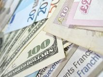 Banknotes - world money. Close-up view of banknotes of various currencies (US dollars, British pounds, Euros and Swiss Francs), with selective focus royalty free stock photo