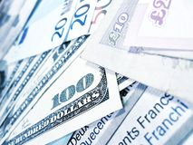 Banknotes - world money. Close-up view of banknotes of various currencies (US dollars, British pounds, Euros and Swiss Francs), with selective focus and bluish royalty free stock images