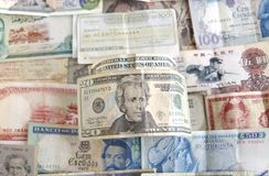 Banknotes from the World and the US. Old cash money from different countries around the world. With a twenty dollar US dollar bill on top Stock Photos
