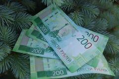 Banknoty Dwie?cie Rosyjskich rubli Got?wkowy papierowy zielony pieni?dze na zielonej ?wierczynie zdjęcia stock