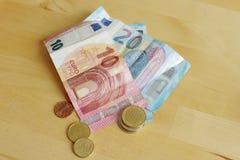 Banknoty i monety na stole zdjęcie stock