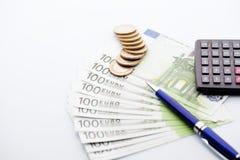 Banknoty, monety, błękitny pióro i kalkulator na odosobnionym backgr, Zdjęcia Royalty Free