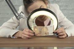 Bankowiec sprawdzał pieniądze dla autentyczności fotografia stock