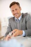 Bankowiec trzyma kredytową kartę z popielatym kostiumem obrazy stock