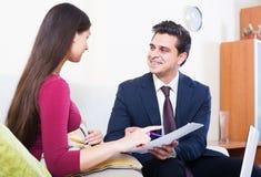 Bankowość agent z ładnej oferty ordynacyjnym klientem w domu Obraz Royalty Free