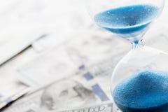 Bankrörelse-, betalning- och skuldbegrepp Dollarpengar och timglas royaltyfria bilder