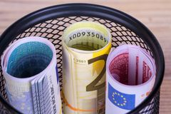 Bankroll Cash Euro Banknotes in Garbage Basket. Focused on consuming in finance concept on wooden background Royalty Free Stock Photos