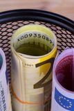 Bankroll Cash Euro Banknotes in Garbage Basket. Focused on consuming in finance concept on wooden background Stock Images
