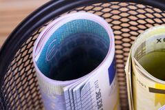 Bankroll Cash Euro Banknotes in Garbage Basket. Focused on consuming in finance concept on wooden background Royalty Free Stock Photo