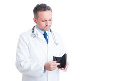 Bankrotter männlicher Doktor oder Mediziner, die leere Geldbörse überprüfen Stockbild