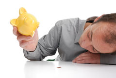 Bankrupt. Man trying to rob the piggy bank Royalty Free Stock Image