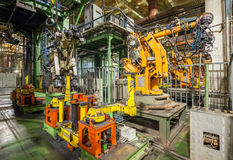 Bankrupt and abandoned automobile plant. Yellow robots welding cars in a production line. Stock Photo