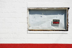 Bankrupt business. Boarded up white window of bankrupt business with Sorry we're closed sign Royalty Free Stock Photo