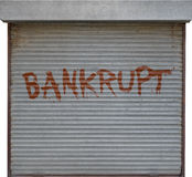 Bankrupt business. Image of a shop shutter down with bankrupt written in paint royalty free stock photo
