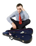 Bankrupt businessman. Desperate bankrupt businessman sitting by a violin case and a few coins - isolated stock image