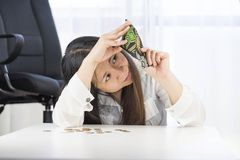 A bankrupt, broke and frustrated woman is having financial problems with coins left on the table and an empty wallet. stock image