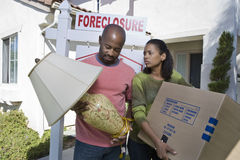 Bankrupt Couple With Lamp And Cardboard Box. Multiethnic bankrupt couple carrying lamp and cardboard box while moving out of house royalty free stock photos