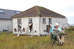 Bankrupt retired businessman. Photo of a retired man yawning over his paper whilst his home is in ruins due to bankruptcy Stock Photography