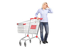 Bankrupt woman posing next to a shopping cart. A bankrupt woman posing next to an empty shopping cart isolated on white background stock photo