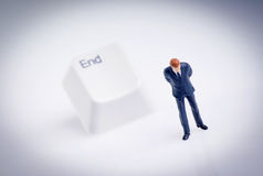Bankruptcy. Tiny figure of businessman stands in front of end key Stock Photo