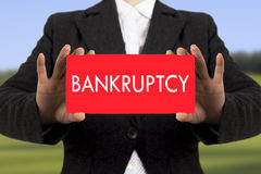 Bankruptcy. Businesswoman in a black jacket shows a card with the inscription bankruptcy. Selective focus Royalty Free Stock Photo