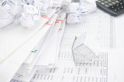 Bankruptcy of house and paper ball with stack of paperwork Royalty Free Stock Photo