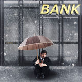 Bankruptcy. Man sitting in front of a bank Royalty Free Stock Photo