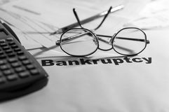 Bankruptcy notification,calculator, eyeglass, pencil. Bankruptcy notification,calculator, eyeglass, pencil and unpaid bills in the background, in black and Stock Photos