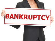Bankruptcy sign. Business woman holding white paper sign saying bankruptcy in red letters Stock Photos
