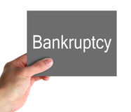 Bankruptcy Sign. A hand holding gray paper sign saying bankruptcy in white letters royalty free stock photos